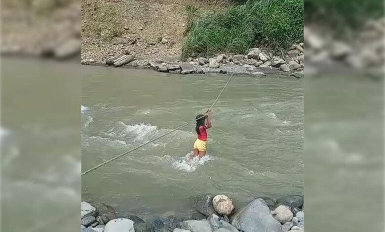 Niña cruza el corrientoso río Agüita en Risaralda donde puente colapsó